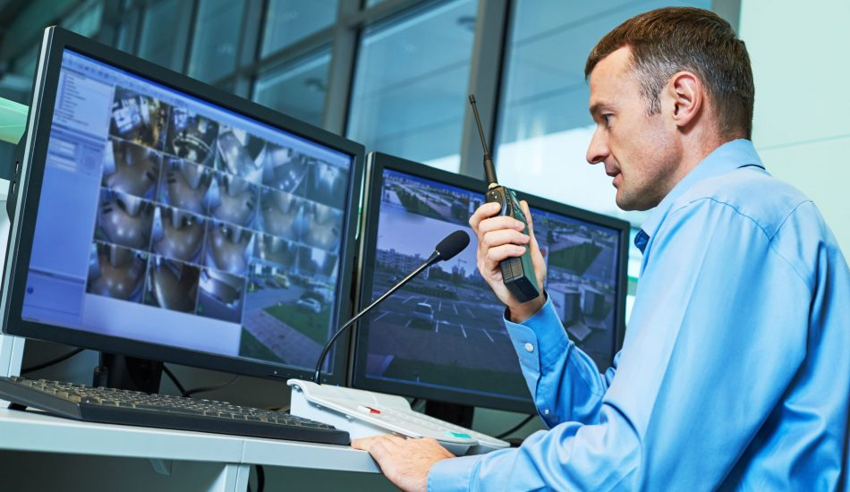 Security-guard-working-monitoring-screens-dual-monitors-systems-surveillance-scaled